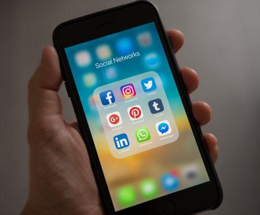 Ein Handydisplay zeigt einen Ordner mit verschiedenen Social Media Apps zur Auswahl.