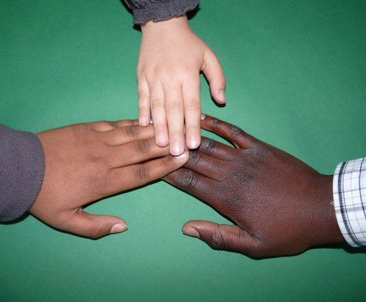 Menschen unterschiedlichen Alters und unterschiedlicher Hautfarbe berühren sich an den Fingerspitzen.
