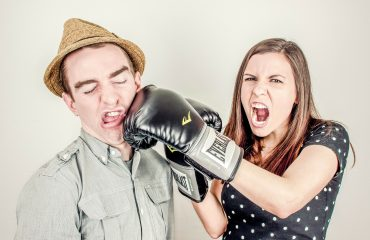 Eine Frau boxt einen Mann mit einem Boxhandschuh ins Gesicht (witzige Darstellung).