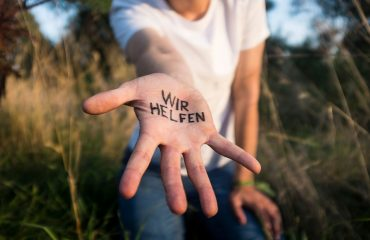 """Ausgestreckte Hand mit Schriftzug """"Wir helfen"""""""