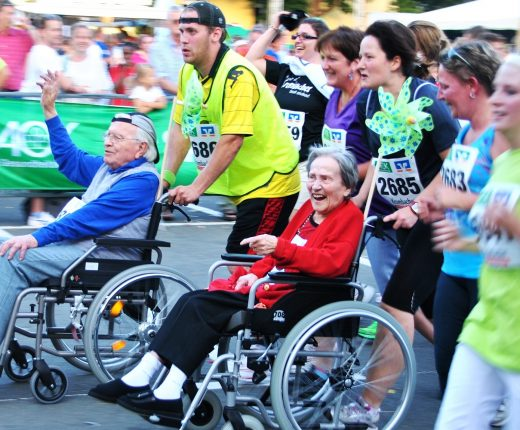 Bei einem Firmenrennen nehmen Menschen mit und ohne Gehbehinderung teil.