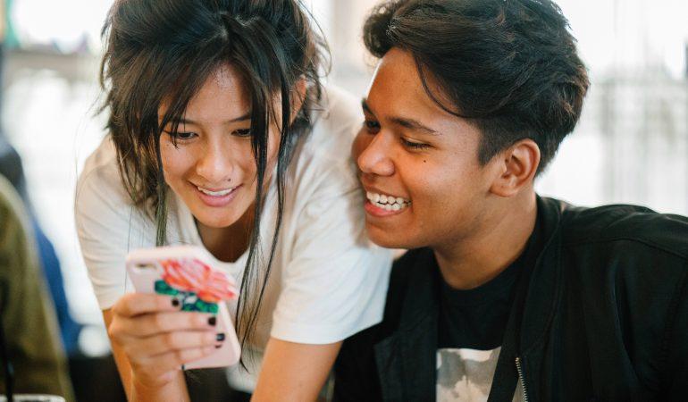 eine junge Frau steht schräg hinter einem jungen Mann. Sie schauen zusammen auf ihr Smartphone und lachen.