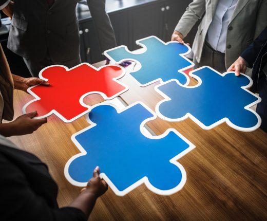 Eine Gruppe von Menschen versucht überdimensionierte Puzzleteile zusammenzuhalten.
