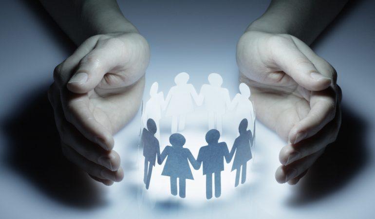 Schützende Hände um einen Papierschnitt von Menschen