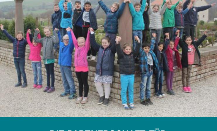 Eine Gruppe Kinder in bunten Jacken hält sich ab den Händen.
