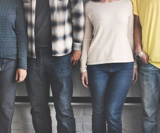 Eine Gruppe von Menschen unterschiedlicher Hautfarbe und Kleidung lehnt gegen eine Wand im urbanen Raum.