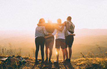 Eine Gruppe Jugendlicher, die sich umarmen, ist von hinten zu sehen