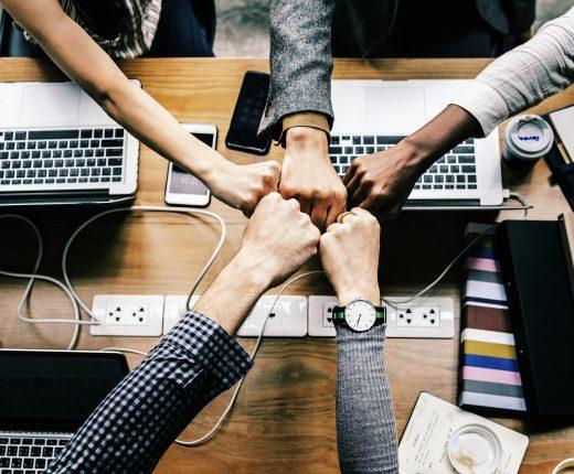 Teamwork - Fünf Hände kommen über einem Tisch mit Laptops und Medien zusammen