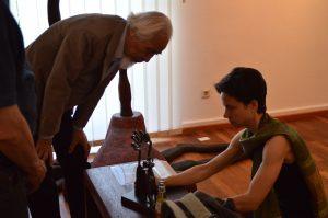 Seiji Kimoto steht mit Frau Dr. Paul über eine kleine Skulptur gebeugt