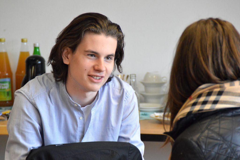 Porträt eines interessierten Jugendlichen im Gespräch im Workshop, angeschnitten sieht man den Hinterkopf des Gegenübers