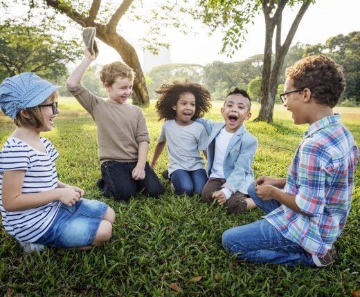 Kinder sitzen lebhaft in einem Halbkreis in der Natur
