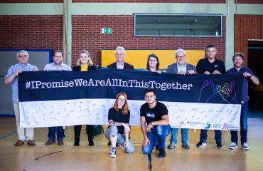 Die Projektförderer und das ABZ halten einen Banner mit dem Motto I Promise We Are All In This Together hoch, davor knien die YouTuberin Fräulein Chaos und Tome