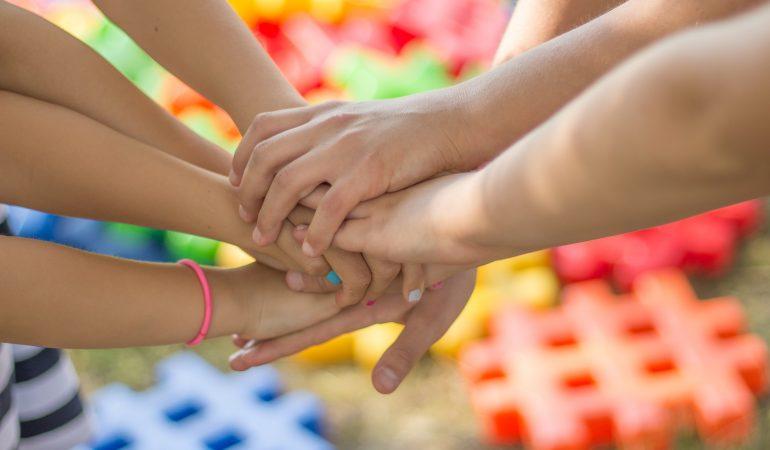 Viele Hände fassen sich vor buntem Hintergrund aneinander