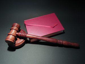 Ein Richterhammer liegt neben einem Buch