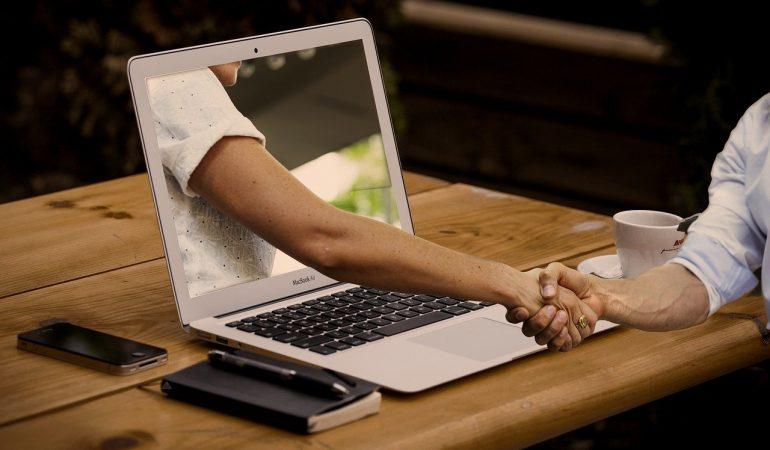 Eine Hand greift aus dem Bildschirm heraus die Hand von jemand der vor dem Laptop sitzt