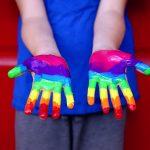 Ein paar bunt angemalte Kinderhände in Regenbogenfarben