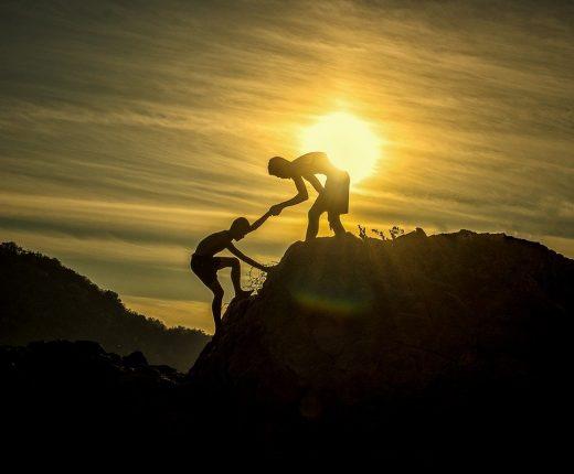 Ein Kletterer hilft dem anderen beim Aufstieg