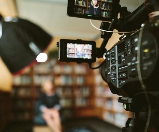 eine Kamera im Vordergrund gilt auf einen verschwommenen Hintergrund. Ein Bücherregal und eine Person sind schemenhaft zu erkennen.