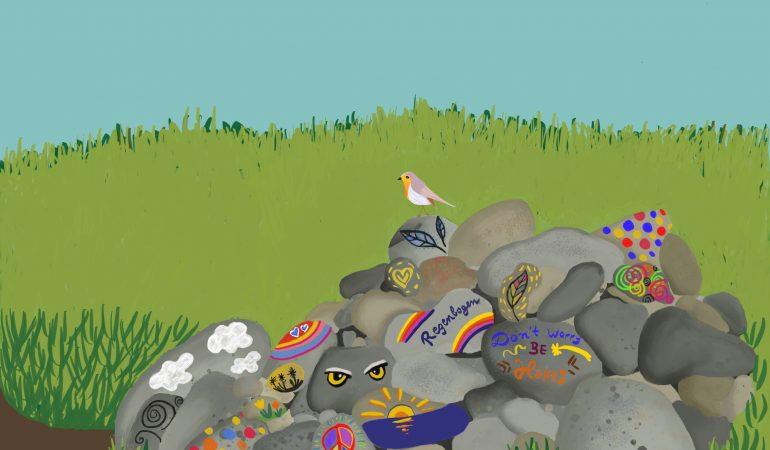 Ein Steinhaufen mit bunten Steinen. Auf einem Stein sitzt ein Vogel.