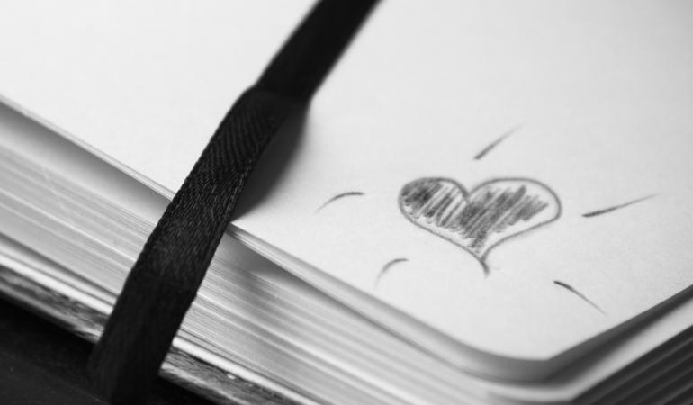 Die Ecke eines Notizbuches ist zu sehen, worauf ein Herz gezeichnet ist