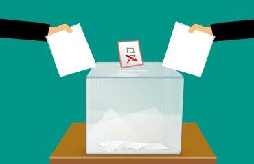 Zwei Stimmzettel, die in eine Wahlurne geworfen werden